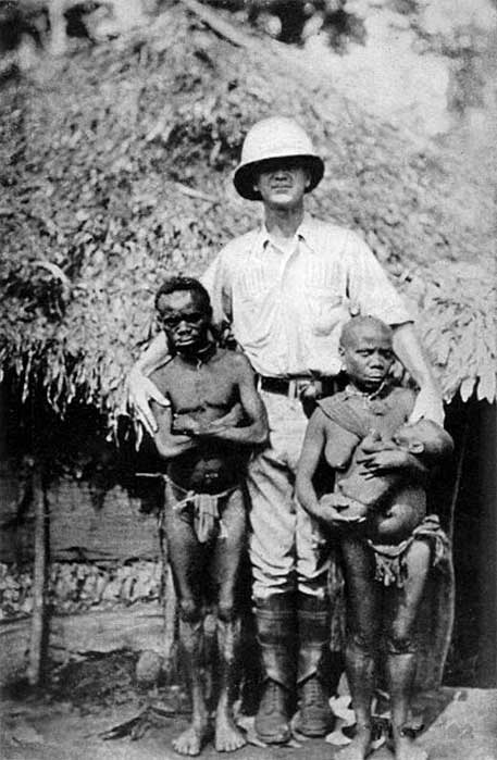 1921 photo of African pygmies and a European explorer. (Public Domain)