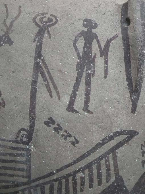 A ritual scene painted on a Predynastic pottery jar depicts multiple S-shaped motifs and a man holding a curved implement similar to the tattoo designs found on the woman.