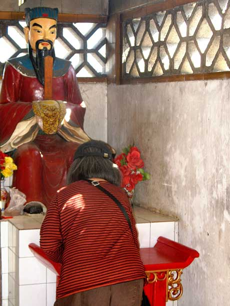 A woman makes an offering to a Chinese Kitchen God shrine. (CC BY-NC-SA 2.0)