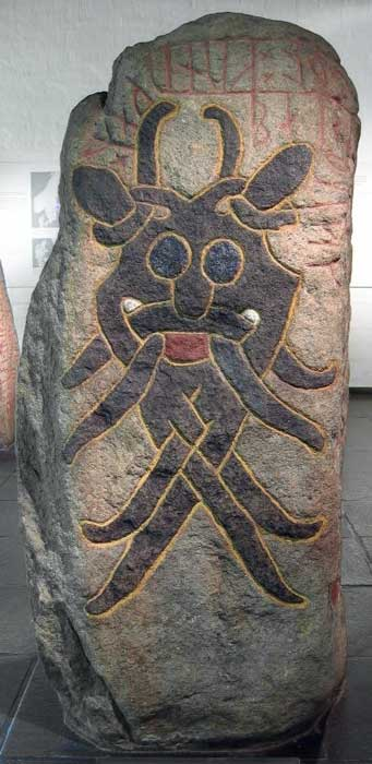 """The Aarhus Mask Stone displays a very symmetrical mask with a happy or lunatic expression. The nose and eyes are very much like the Sjellebro Mask Stone. The runes say: """"Gunnulfr and Eygautr/Auðgautr and Áslakr and Hrólfr raised this stone in memory of Fúl, their partner, who died when kings fought."""" (Gardar Rurak / CC BY-SA 4.0)"""