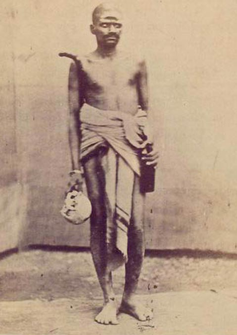 An Aghori carrying a skull and alcohol. (circa 1875)