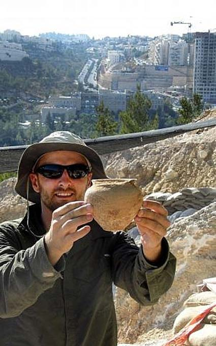 Alex Wigman, an Israel Antiquities Authority archaeologist, holds a small jar from the Canaanite tomb in Jerusalem. (Shua Kisilevitz, Israel Antiquities Authority)