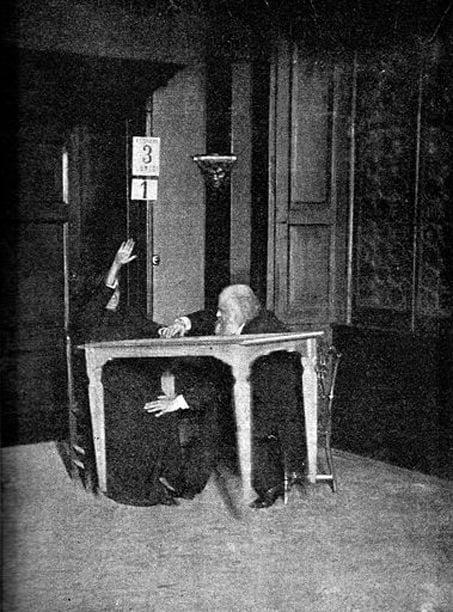 """Alexandr Aksakov (right) """"controls"""" while Palladino levitates table, Milan. (1892)"""