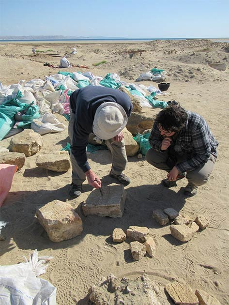 Archaeologists examine a block carved with hieroglyphs at the site. (I. Zych / PAP)