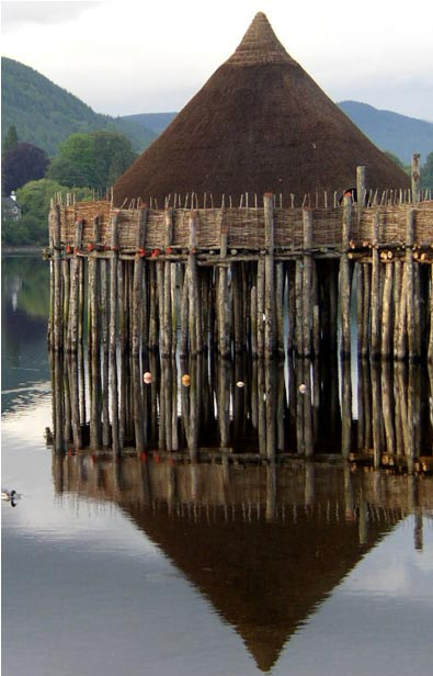 The newly-discovered timber posts are believed to have been stilts upon which the crannog was built. Reconstructed crannog on Loch Tay, Scotland