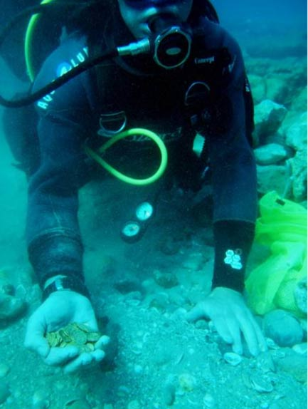 Diver holding a handful of the newly-discovered coins in Israel.