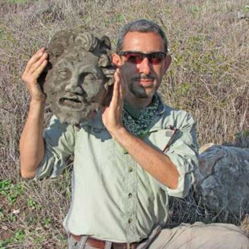 Dr. Michael Eisenberg holding up the bronze mask of Pan.