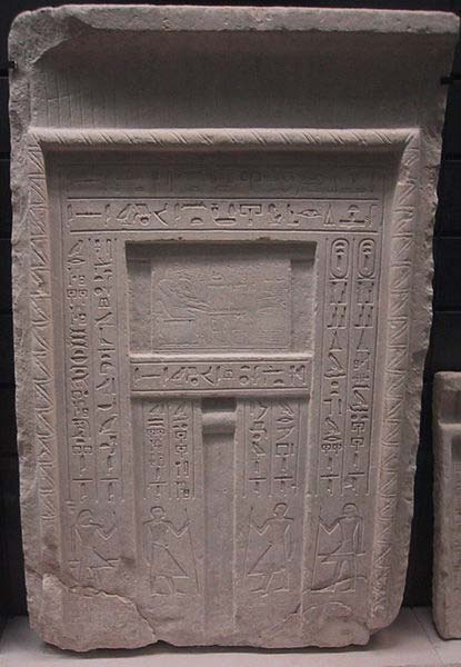 A typical false door to an Egyptian tomb - the deceased is shown above the central niche in front of a table of offerings, and inscriptions listing offerings for the deceased are carved along the side panels.