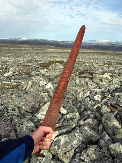 Einar Åmbakk holding the sword, just moments after it was discovered.