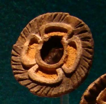 Four-petalled flower-mirror with feathered rim from Teotihuacan.