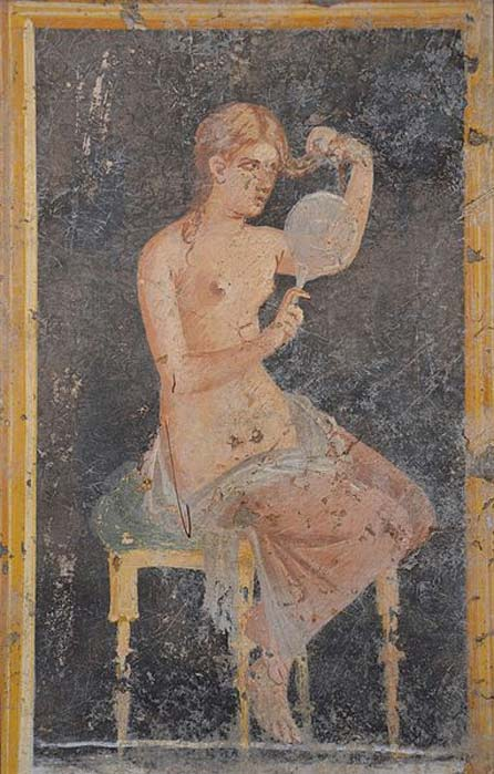 Fresco showing a woman looking in a mirror as she dresses (or undresses) her hair, from the Villa of Arianna at Stabiae (Castellammare di Stabia), 1st century AD, Naples National Archaeological Museum. (Carole Raddato/CC BY SA 2.0)
