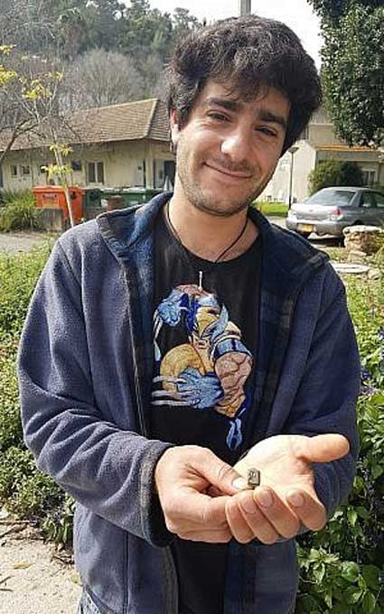 Gardener Dekel Ben-Shitrit with the ring he found while weeding. (Nir Distelfeld, Israel Antiquities Authority)