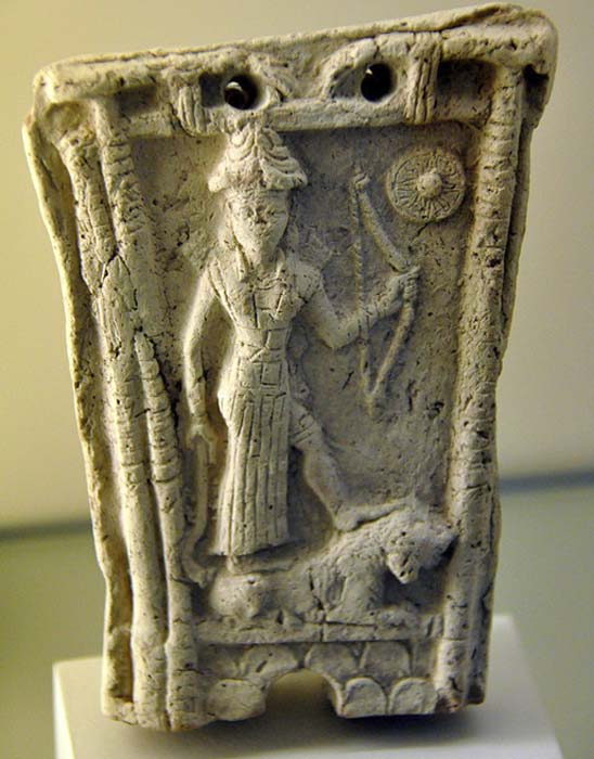 Goddess Ishtar (Inanna) stands on the back of an animal (probably a lion). She holds a bow with her left hand while the right hand grasps what appears to be a crook or a sickle-like object. The symbol of the god Shamash (Utu) can be seen at the upper right corner (CC by SA 4.0).