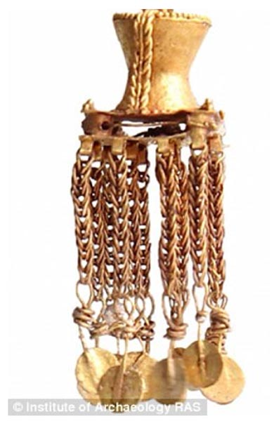 Gold and silver jewelry was found in the woman's grave, including these gold earrings