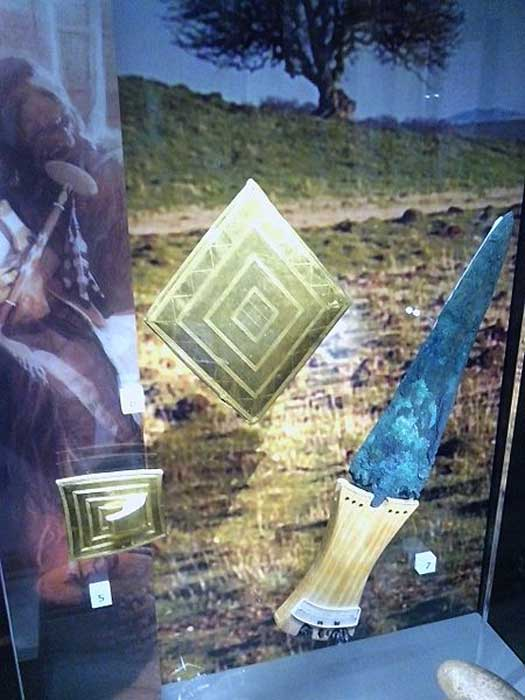Gold lozenge, gold belt buckle, copper dagger. Bronze Age grave goods from Wilsford G5, Bush Barrow. Now in the Wiltshire Museum, Devizes.