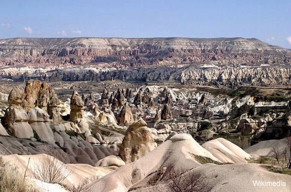 The town Göreme with rock houses in front of the spectacularly coloured valleys nearby.
