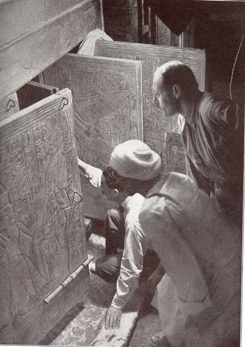 Howard Carter and associates opening the shrine doors in the burial chamber.