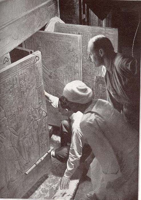 Howard Carter (kneeling), an Egyptian workman, and Arthur Callender at doors of burial shrines in Pharaoh Tutankhamen's tomb.