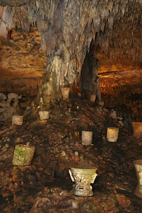 Incense burners around the tree-like column in the Balankanché Cavern