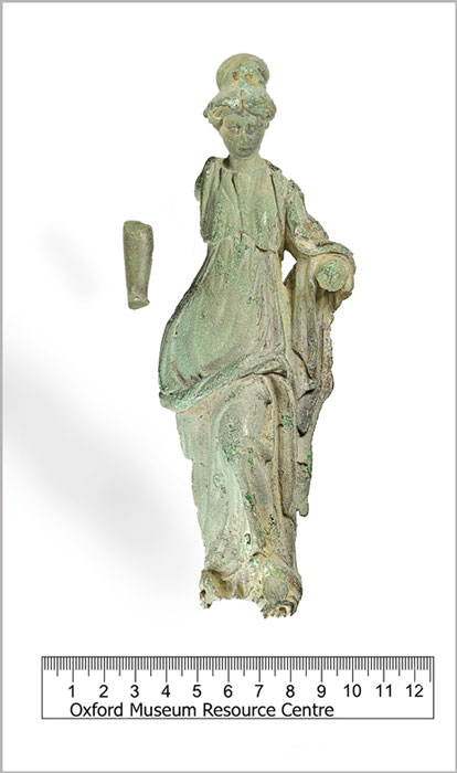 Incomplete cast copper and lead alloy three-dimensional statue of the Roman goddess Minerva, dating to the period AD 43-200. The statue is in three pieces, with the head and part of the lower right arm being detached from the body. The lower left arm and possibly a small section of the base is also missing. (Oxfordshire County Council / CC BY-SA 4.0)