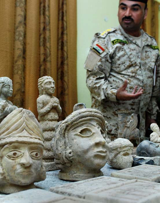 Iraqi Col. Ali Sabah, displays ancient artefacts Iraqi Security Forces discovered in 2008, during two raids in northern Basra. (Public Domain)