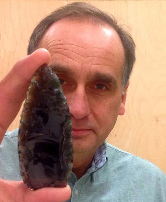 Karl Hutchings, an archaeologist at Thompson Rivers University in Canada, holds a Clovis spear point. (Karl Hutchings / Thompson Rivers University)