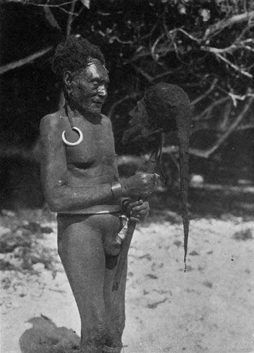 An image from the 1934 book 'Malekula: A Vanishing People in the New Hebrides', showing a man holding a cured head wearing a spider web cap.