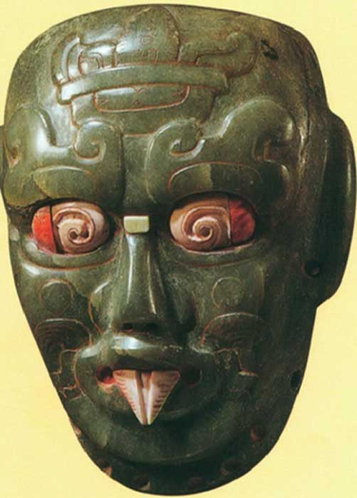 A Maya jade mask with a shark tooth from a tomb in Rio Azul, Peten, Guatemala.