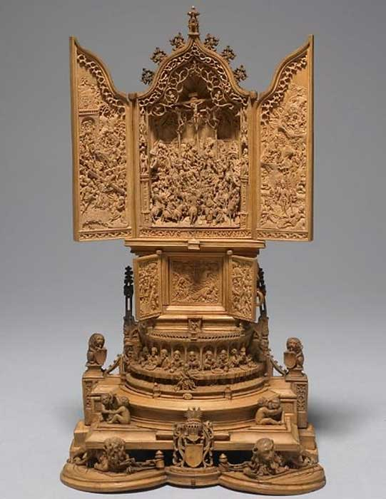 Miniature altar-piece; boxwood; upper section is a triptych with carvings of ogee arches, Crucifixion in the center, and numerous figures. Left wing: Bearing of the Cross with Sacrifice of Isaac in distance; right: Resurrection, with Entombment and other scenes in background; second stage is a smaller triptych with Agony in the Garden and, on the leaves, the Betrayal; this rests on semi-circular arcade with the Last Supper; each side has a carving of a seated lion grasping a shield; rectangular base with wrestling children filling the angles; whole rests on two recumbent lions chained to posts; between them is shield with a helmet, mantlings and crest.