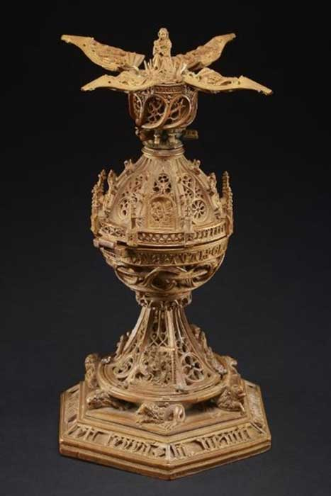 Miniature tabernacle; carved in openwork boxwood with scenes from Life and Passion of Christ; pinnacle surmounted by Pelican in her piety, which is removable, thus releasing four petals into which the upper part is divided; these are depressed by a ratchet while figure of Virgin and Child rise in center.
