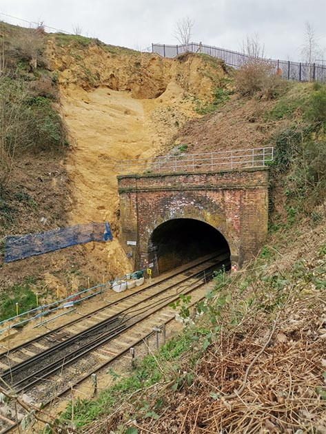 Network Rail workers were fixing a landslide, when they uncovered a small cave believed to be from the 14th century. Pictured is the outside of the cave next to the railway. (Archaeology South East)
