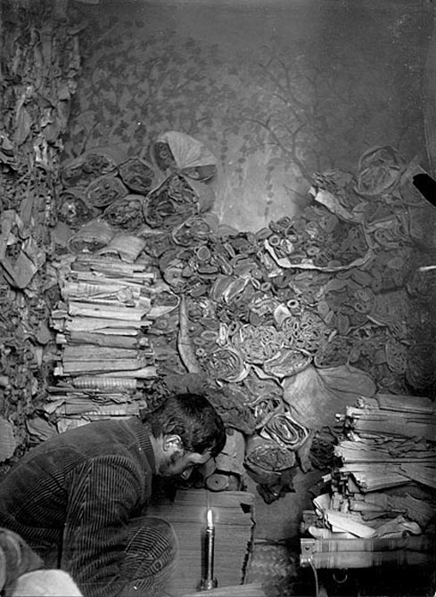 Paul Pelliot examining manuscripts in the Library Cave, 1908.