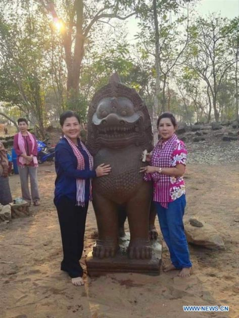 People posing for photos with a newly discovered 7ft (2m) tall lion statue in Banteay Meanchey Province. (Photo released by Cambodia's Culture Ministry / Xinhuanet)