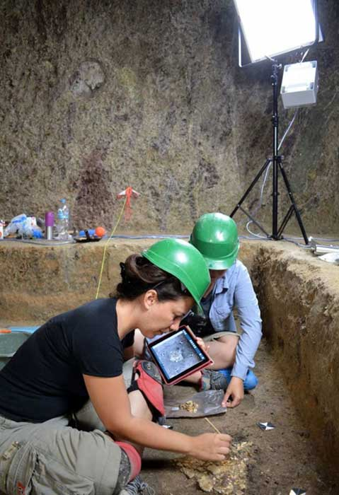 Recording the bones in the burial chamber's interior.