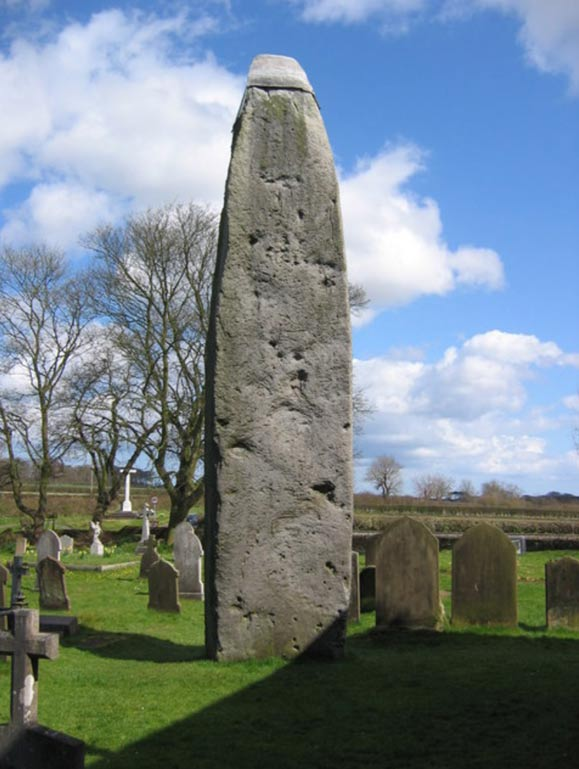 Rudston Monolith, East Riding of Yorkshire, England. The stone stands almost 26 feet high next to Rudston Parish Church of all Saints. Made form Moor Grit Conglomerate from the Late Neolithic Period. This stone can be found in the Cleveland Hills inland from Whitby. This view to its wide face looking NE.