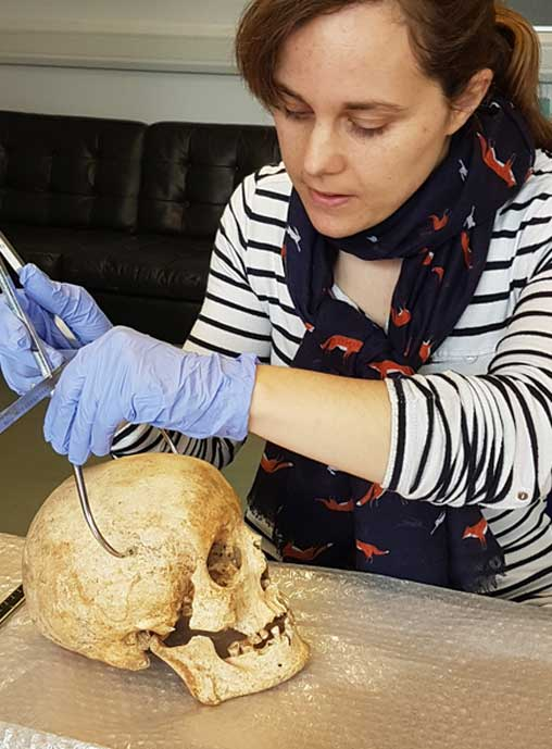 Dr. Sarah Inskip examines the skull of Context 958.