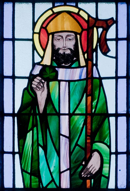 St. Patrick depicted with shamrock in detail of stained glass window in St. Benin's Church, Wicklow, Ireland.