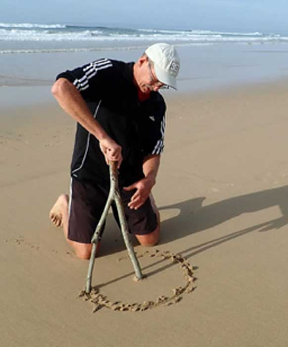 The author demonstrates how a forked stick may have been used by a kneeling human to create a circular pattern in the sand. (Linda Helm / The Conversation)