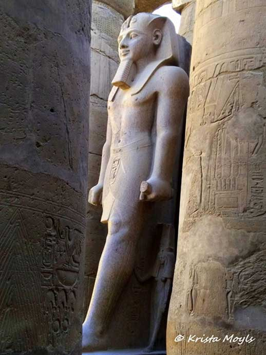 The grandiose and wealthy Karnak temple, dedicated to the Theban triad of Amun, Mut and Khonsu, is the largest religious building ever made. Covering about 200 acres (1.5 km by 0.8 km), it was a place of pilgrimage for nearly 2000 years. Here, an imposing sculpture of Ramesses II stands proud in the precincts of the temple.