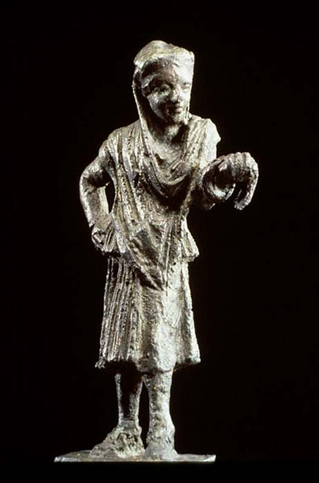The half-mask over the eyes and nose identifies the figure as an actor. He wears a man's conical cap but female garments, following the Greek custom of men playing the roles of women.