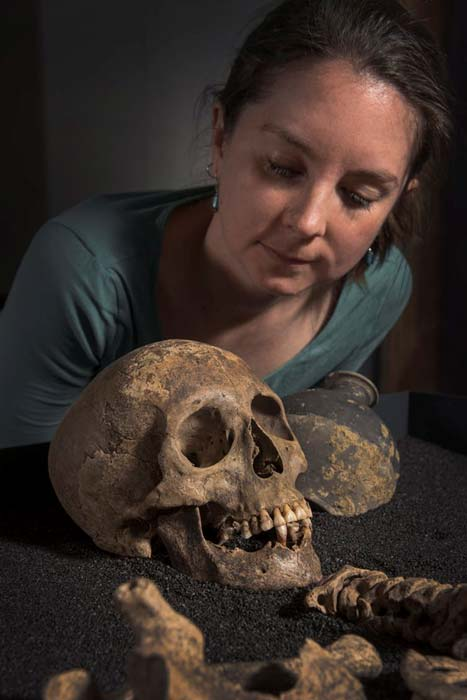 The skull of a woman buried in Southwark with curator Meriel Jeater. © Museum of London