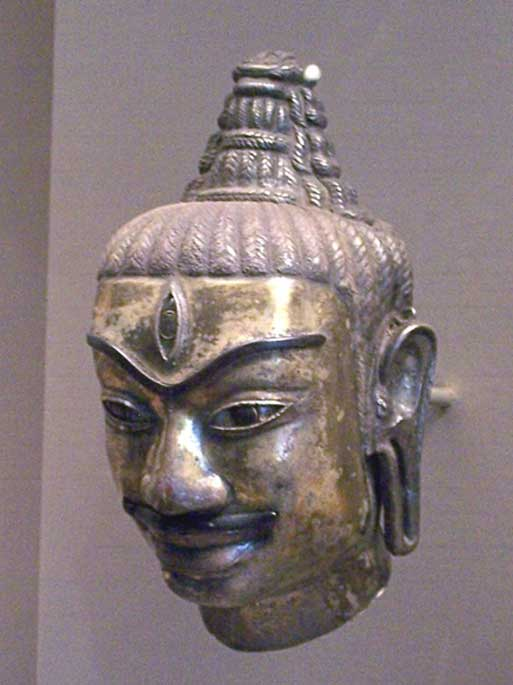 'This Cham head of Shiva was made of electrum around 800. It's a decorated kosa, or metal sleeve fitted to a liṅgam. One can recognize Shiva by the tall chignon hairstyle and by the third eye in the middle of his forehead.'