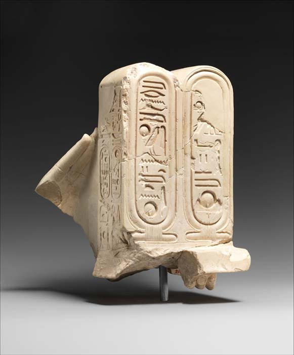 This object was assembled from pieces found in the Sanctuary of the Great Aten Temple. The double cartouches of the Aten's early name are presented by the two hands of a figure that is now missing. These hands and cartouches in a very fine indurated limestone appear to have belonged to a very special statue at Amarna. Metropolitan Museum of Art, New York.