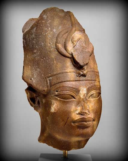 This quartzite head shows King Amenhotep III wearing the Blue Crown (also called the War Crown). The facial features show the stylistic elements of his later representations: highly arched brows, elongated almond-shaped eyes, and full, sharply outlined lips. Metropolitan Museum of Art, New York.