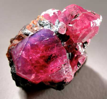 Two crystals of lustrous and translucent, cherry red ruby with exquisite micro-details on the faces and sharp bevelled edges. The larger one, exhibiting superb crystal form, measures 1.5 cm across. Recovered from: Winza, Mpapwa, Mpapwa (Mpwampwa) District, Dodoma region, Tanzania. (CC BY-SA 3.0)