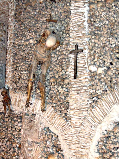 Two human corpses, corresponding to an adult male and young child appear chained to a wall of the Chapel of Bones.