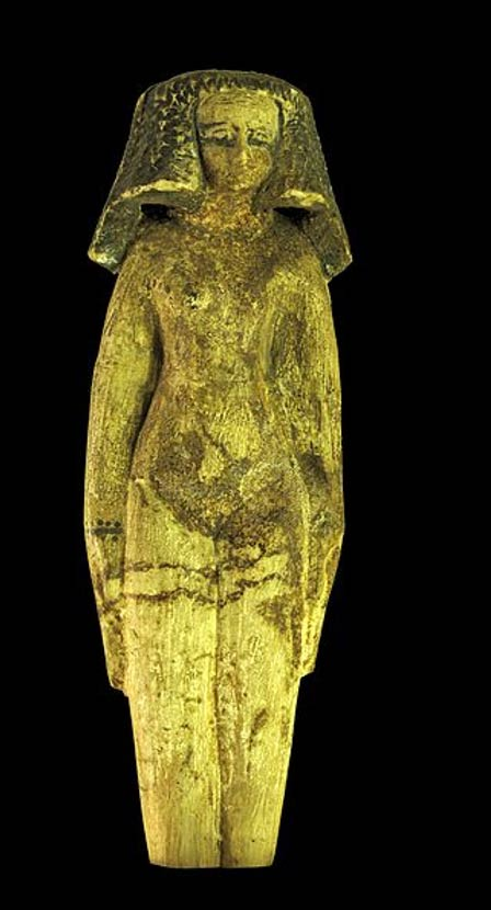 Ushabti of a Concubine; along with the naked body, jewelry underlying the breasts and shaved pubis with visible vulva, the heavy wig gives an erotic connotation to the statuette. Painted wood, Middle Kingdom Egypt.