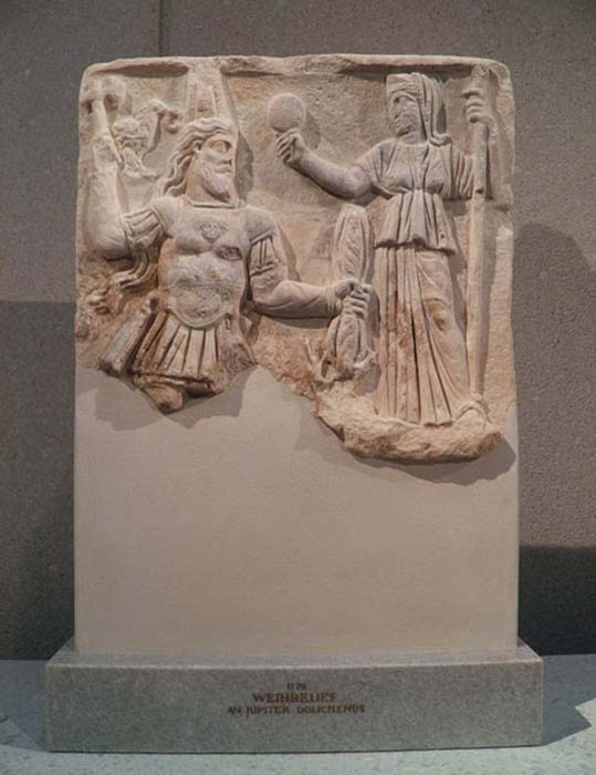 Votive relief to Jupiter Dolichenus and Juno, Jupiter with tiara, sword, an ax and lightning bundle, Juno has a mirror and a scepter, 3rd century AD, from Rome, Neues Museum, Berlin.