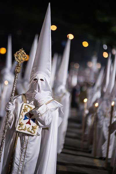 White-cloaked participants march in Holy Week (CC by SA 4.0)