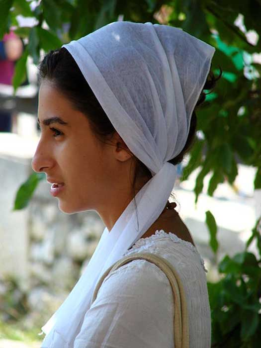 Young woman in traditional dress at a religious ceremony, Constanta, Romania. June 2007.